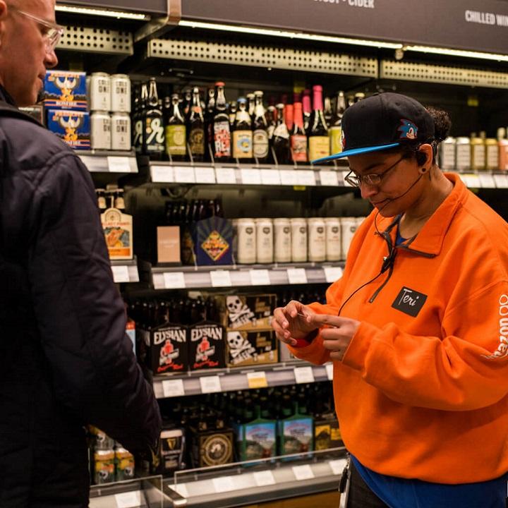 Сотрудник Amazon Go проверяет документы у покупателей, желающих приобрести алкоголь